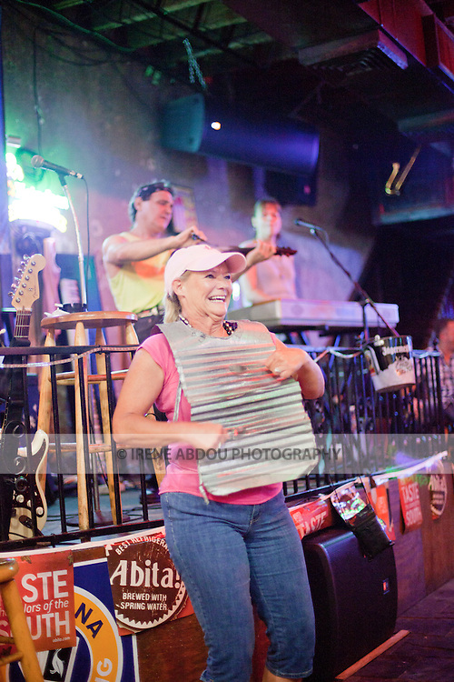The Danny T Band plays a mean zydeco at a bar on New Orleans, Louisiana's famed Bourbon Street.  Pulled in from the audience, a tourist plays the washboard, a low-tech percussion instrument made from a sheet of metal, which figures prominently in Zydeco.