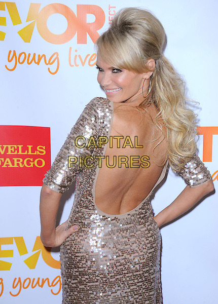 """Kristin Chenoweth.The Trevor Project's """"Trevor Live"""" 2012 held at the Hollywood Palladium, Hollywood, California, USA..December 2nd, 2012.half length dress hands on hips backless back behind rear looking over shoulder silver gold  sequins sequined smiling hoop earrings                           .CAP/RKE/DVS.©DVS/RockinExposures/Capital Pictures."""