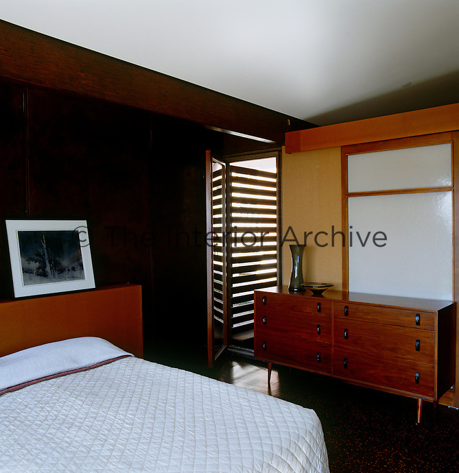 The bedroom is sparsely furnished with a retro wooden chest of drawers