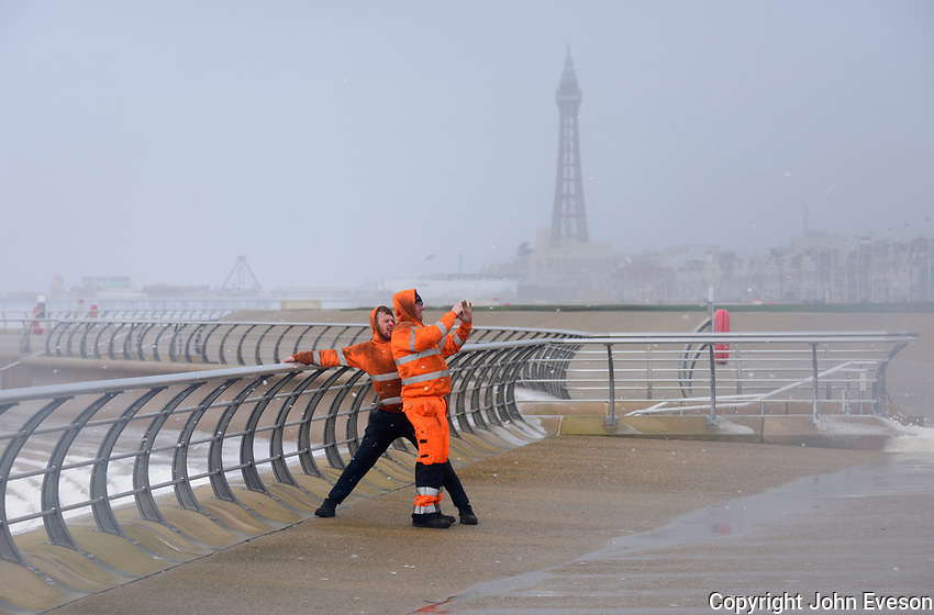 Two workers take a selfie as winds reach 90 mph at Blackpool, Lancashire during storm Doris.