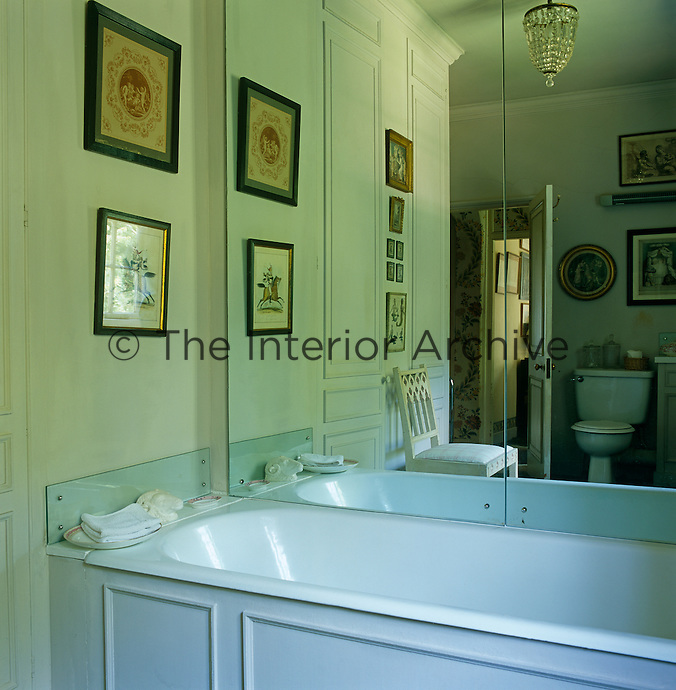 Mirror panels down one side of the bath enhance the size of the bathroom