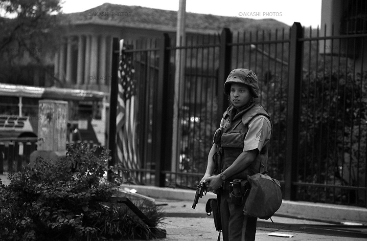 Nairobi, Kenya.August 7, 1998.The U.S. Embassy was sealed off soon after the explosion. A U.S. marine stands guard outside the damaged embassy compound with a fallen American flag on the fence..©Toru Morimoto