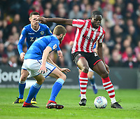 Lincoln City's John Akinde shields the ball from  Macclesfield Town's Fiacre Kelleher<br /> <br /> Photographer Andrew Vaughan/CameraSport<br /> <br /> The EFL Sky Bet League Two - Lincoln City v Macclesfield Town - Saturday 30th March 2019 - Sincil Bank - Lincoln<br /> <br /> World Copyright © 2019 CameraSport. All rights reserved. 43 Linden Ave. Countesthorpe. Leicester. England. LE8 5PG - Tel: +44 (0) 116 277 4147 - admin@camerasport.com - www.camerasport.com
