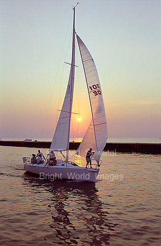 A sailboat gliding into a harbor as the sun sets.