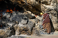 Incense burns at the holy shrine while a Tibetan Buddhist pilgrim with prayer wheel kneels on the rubbing-stones, worn smooth over the ages, practicing an ancient Bon shamanistic ritual to the mountain deity.  On the 8 km Lingkhora pilgrim circuit around the old city perimeter, Lhasa, Tibet.