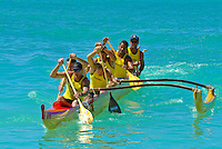 A lifeguard team paddles a Hawaiian outrigger canoe to the finish in a race during legendary surfer and waterman Duke Kahanamoku 's birthday celebration. Waikiki Beach.