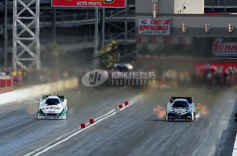 Apr. 2, 2011; Las Vegas, NV, USA: NHRA funny car driver Mike Neff (left) races alongside Matt Hagan during qualifying for the Summitracing.com Nationals at The Strip in Las Vegas. Mandatory Credit: Mark J. Rebilas-