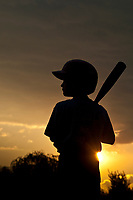 Young boy stands at home plate waiting instructions from his coach during practice following a baseball game as the sun set near the end of youth summer baseball season.