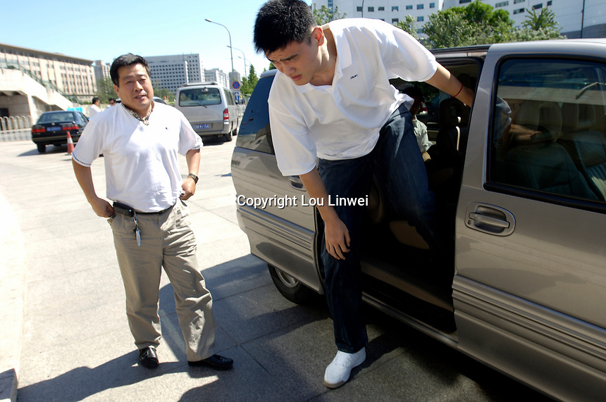 NBA Houston Rockets player Yao Ming gets out of a mini-bus to attend a press conference for the 2007 Special Olympics while a man plays with a basketball in Beijing, China.  July 21, 2006. (photo by Lou Linwei/Sinopix)