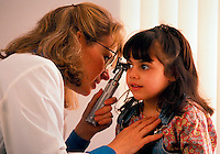 Doctor examining her young patient's ears during a check-up.