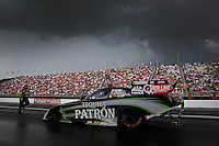 Aug. 31, 2013; Clermont, IN, USA: NHRA funny car driver Alexis DeJoria is backed up by a crew member under heavy clouds during qualifying for the US Nationals at Lucas Oil Raceway. Mandatory Credit: Mark J. Rebilas-