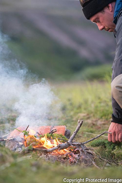 Mann fyrer bål og griller laksefileter. ---- Man grilling salmon filets on open fire.