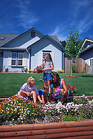 Mother and children planting annuals in garden