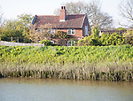 Riverside cottage on the banks of the River Alde at Snape, Suffolk, England