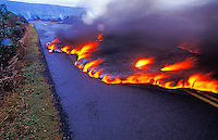 Dramatic shot of lava flowing over the center yellow lines of a highway at Kamoamoa on the Big Island.