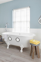 Two portholes turn this classic roll top bath into a play boat when bath time comes around