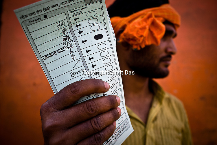 A Bhartiya Janta Party member shows the pamphlets (of the electronic voting machine) demonstrating who to vote during the polling day in Azamgarh, Uttar Pradesh, India. One of the BJP's strong candidates, Ramakant Yadav are one of the many political leaders in UP who have criminal cases against them.