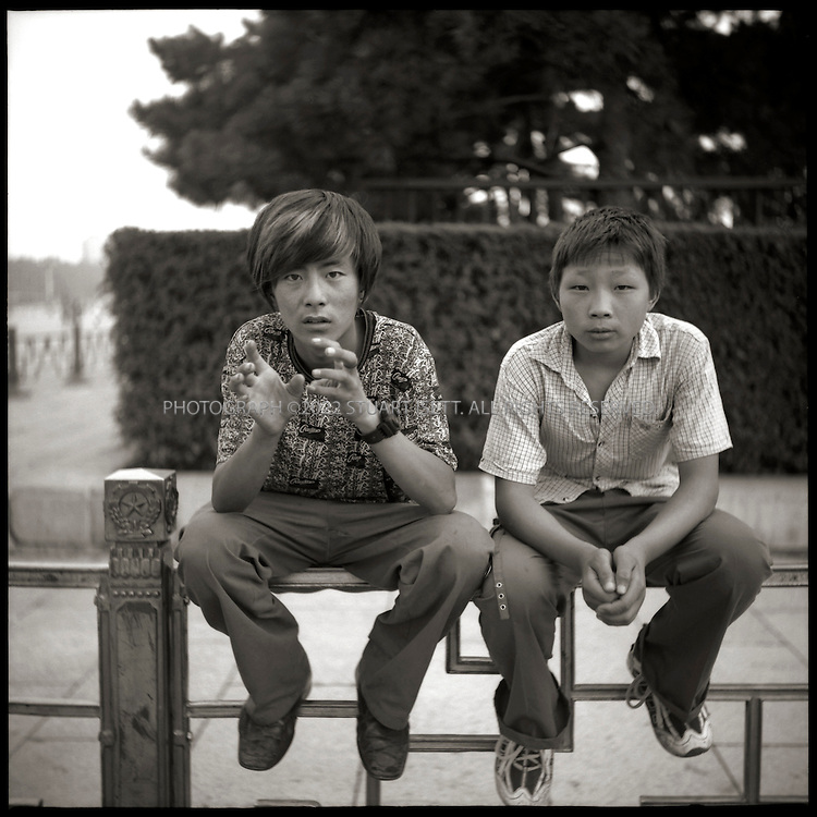 6/26/2005--Beijing, China..Zhang fei, 18 (left) from Shanxi Province and Zhang Hangtao, 16, from Henan province, hand out flyers to tourists near Mao's Mausoleum on Tiananmen Square. ..Photograph By Stuart Isett.All photographs ©2005 Stuart Isett.All rights reserved.