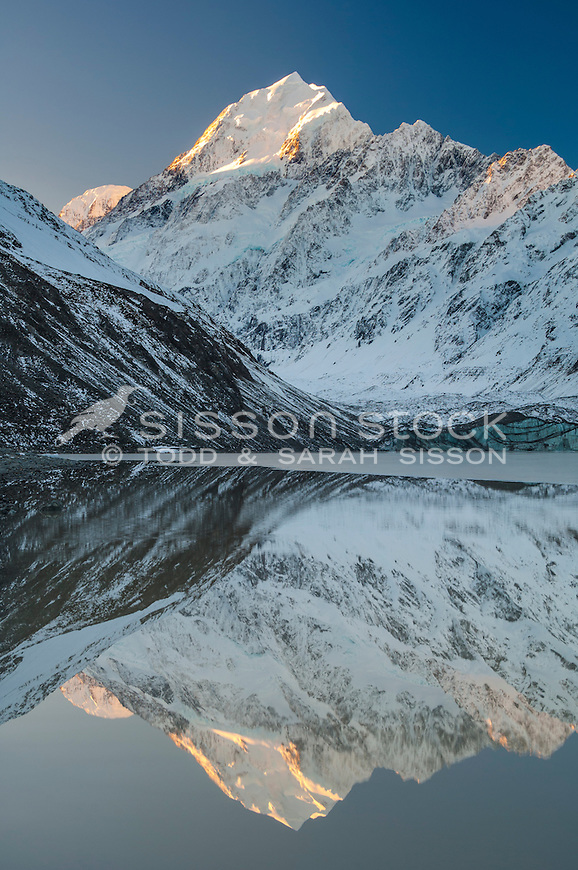 Aoraki Mt Cook & the Southern Alps reflected in Hooker Lake, at sunset.  Cook Range and the Southern Alps from Hooker Glacier Terminal Lake. Aoraki Mt Cook National Park, NZ.