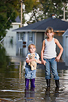 USA, Illinois, Chillicothe, Two girls (2-3, 8-9) holding hands, Standing in water and looking at camera