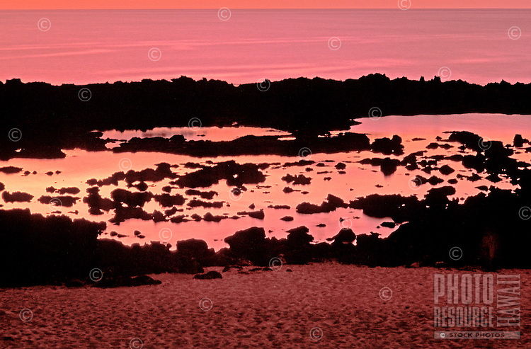 Shark's Cove on the North Shore lit up by the reds and oranges of the sunset