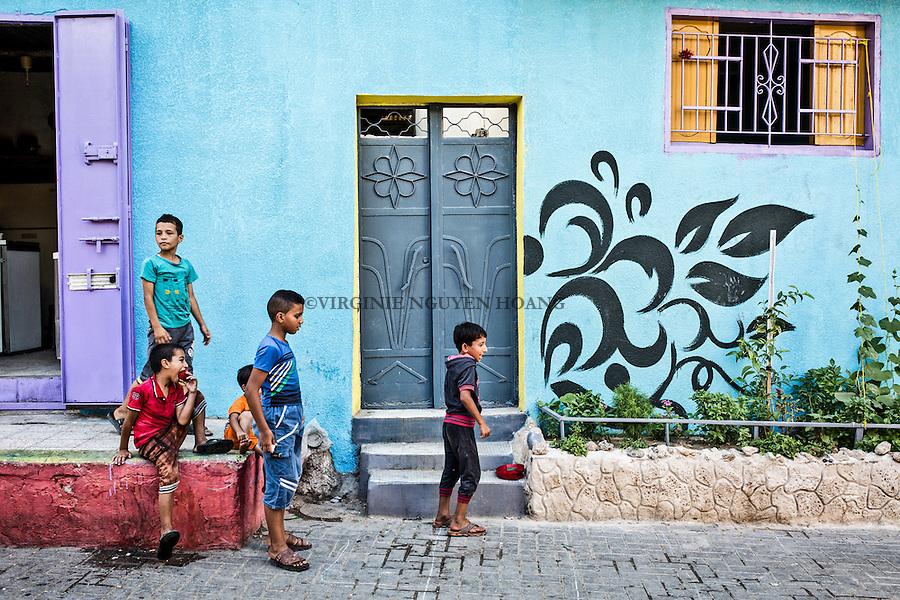 GAZA, Zaytoun: Some boys are playing in the streets of Zaytoun. Behind them, a wall totally blue and purple. Kids of the neighbourhood are very happy about the new look of their streets.  15/08/15<br /> <br /> GAZA , Zaytoun : Des gar&ccedil;ons jouent dans les rues de Zaytoun . Derri&egrave;re eux , un mur totalement bleu et violet. Les enfants du quartier sont tr&egrave;s heureux du nouveau look de leurs rues . 15/08/15