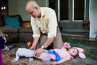 Fred Bermont changes the diaper of daughter Elyse Bermont (age 2.5) before he drops the kids off at day-care in Lexington, Massachusetts, USA, before he goes to work on June 9, 2014. Bermont is the father of two children and shares parenting duties with his wife, Jen Bermont. Fred usually takes care of the morning routine, including feeding, dressing, and dropping the kids off at day-care, and Jen picks them up and watches over them in the afternoon. Fred is a Senior Clinical Standards Specialist at Shire, a pharmaceutical company with headquarters in Lexington.
