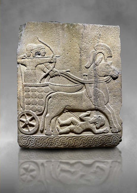 Hittite relief sculpted orthostat stone panel of Long Wall Basalt, Karkamıs, (Kargamıs), Carchemish (Karkemish), 900 - 700 B.C.  Anatolian Civilizations Museum, Ankara, Turkey<br /> <br /> Chariot. One of the two figures in the chariot holds the horse's headstall while the other throws arrows. There is a naked enemy with an arrow in his hip lying face down under the horse's feet. It is thought that this figure is depicted smaller than the other figures since it is an enemy soldier. The tower part of the orthostat is decorated with braiding motifs.<br /> <br /> On a grey art background.
