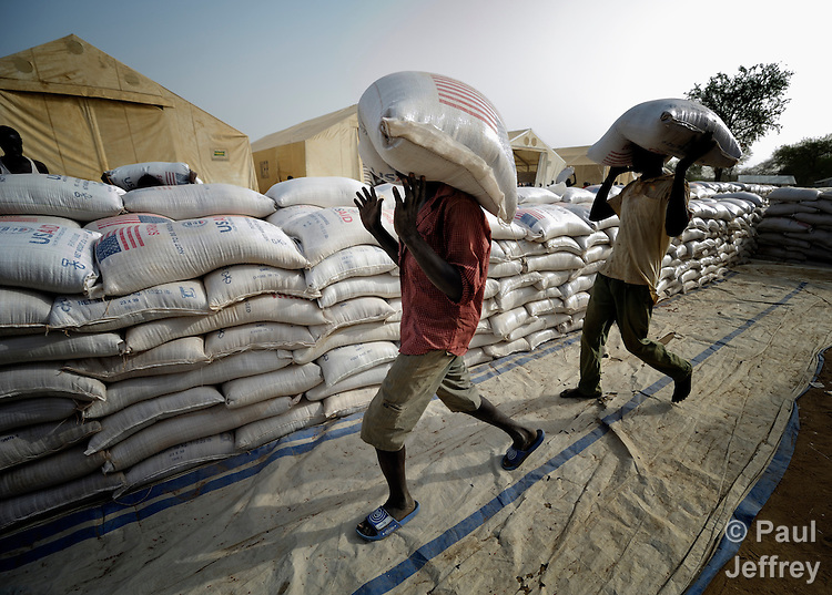Men unload sorghum for displaced families in Agok, a town in the contested Abyei region where tens of thousands of people fled in 2011 after an attack by soldiers and militias from the northern Republic of Sudan on most parts of Abyei. Although the 2005 Comprehensive Peace Agreement called for residents of Abyei--which sits on the border between Sudan and South Sudan--to hold a referendum on whether they wanted to align with the north or the newly independent South Sudan, the government in Khartoum and northern-backed Misseriya nomads, excluded from voting as they only live part of the year in Abyei, blocked the vote and attacked the majority Dinka Ngok population. The African Union has proposed a new peace plan, including a referendum to be held in October 2013, but it has been rejected by the Misseriya and Khartoum. The Catholic parish of Abyei, with support from Caritas South Sudan and other international church partners, has maintained its pastoral presence among the displaced and assisted them with food, shelter, and other relief supplies. The sorghum being unloaded here, a donation by the U.S. government, is part of an aid distribution by the World Food Programme.