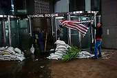 New York, New York.October 30, 2012..The building manager hoists a flag in front of the Financial Square office building in lower Manhattan as workers clean the lobby in the aftermath of Hurricane Sandy.