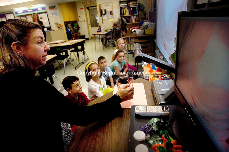 MIDDLEBURY CT. 20 October 2014-102014SV07-Gina Samson, 3rd grade teacher, shows students how calcite and acid react on a smart board with the use of a new document camera the school got through a grant at Middlebury Elementary School in Middlebury Monday. <br /> Steven Valenti Republican-American