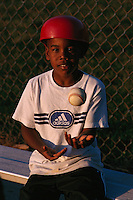 7 year old African American tosses a baseball in the air.