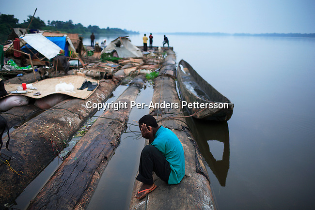 MBANDAKA, DEMOCRATIC REPUBLIC OF CONGO JUNE 27: An unidentified man fights the boredom while traveling on a boat made of big trees on the Congo River on June 27, 2006 outside Mbandaka, Congo, DRC. The boat traveled with about 150 passengers from Bumba to Kinshasa, a journey of about 1300 kilometers. The Congo River is a lifeline for millions of people, who depend on it for transport and trade. Passengers slept in the open, with their goats, pigs and other animals. Boat travel is the only option for most people along the river as there?s no roads or infrastructure. Very few can afford to fly in a plane to the capital Kinshasa. During the Mobuto era, big boats run by the state company ONATRA dominated the river. These boats had cabins and restaurants etc. All the boats are now private and are mainly barges that transport goods. The crews sell tickets to passengers who travel in very bad conditions. The conditions on the boats often resemble conditions in a refugee camp. Congo is planning to hold general elections by July 2006, the first democratic elections in forty years. The Congolese and the international community are hoping that Congo will finally have piece and the country will be rebuilt..(Photo by Per-Anders Pettersson/Getty Images)..