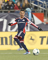 New England Revolution midfielder Diego Fagundez (14) crosses the ball.  In a Major League Soccer (MLS) match, the New England Revolution (blue) defeated Toronto FC (red), 2-0, at Gillette Stadium on May 25, 2013.