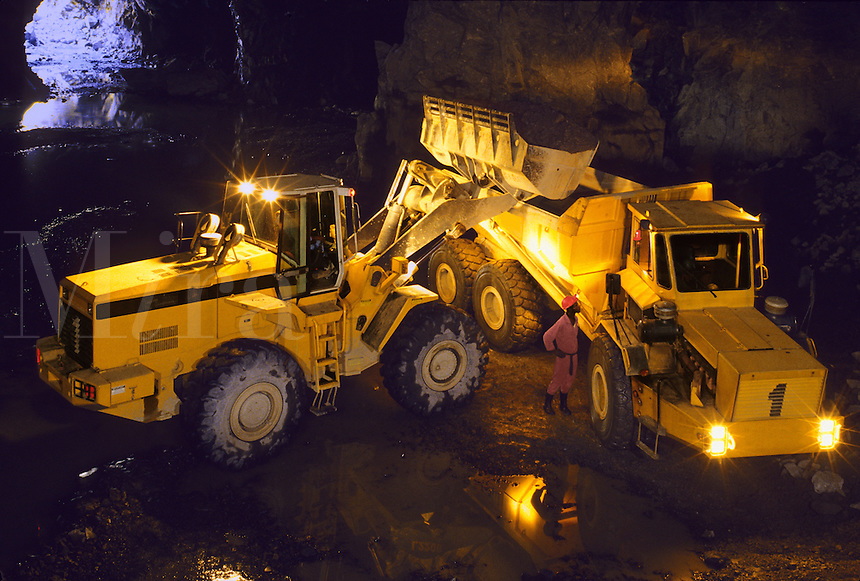 Front loader loading ore into truck in chamber of underground gold mine.  East Africa..