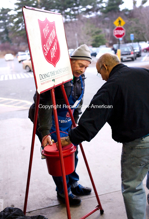 Waterbury, CT- 09 December 2015-120915CM09- Scott Ritchie, a kettle worker with the Salvation Army, collects a donation from Felix Rodriguez, of Waterbury, outside Walmart in Waterbury on Wednesday   Ritchie was collected donations for the Salvation Army, which provides to those in need, among other charitable efforts. Christopher Massa Republican-American