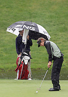 University of New Mexico's Tom Carlson putts his shot on the 9th hole while Southern Tennessee States Draegen Majors huddles under cover from the rain. Rain was off and on all day at Gold Mountain gold course during the first day of the NCAA Division I Regional tournament.
