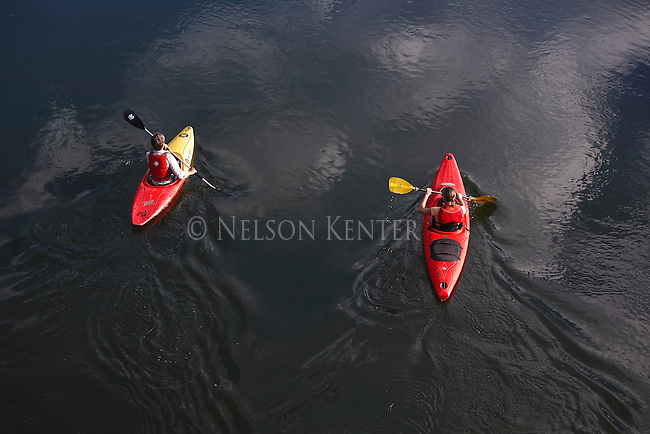 Two kayakers paddle under a bridge over the Clark Fork River above Missoula, Montana