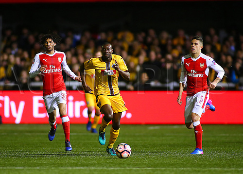 February 20th 2017, The Borough Sports Ground, Sutton, Surrey, England; FA Cup 5th Round football, Sutton United versus Arsenal FC; Bedsente Gomis of Sutton United brings the ball past Arsenal's Mohamed Elneny and Gabriel Paulista