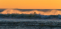 A surfer catches some large waves at sunset off Kawaihae on the Big Island.