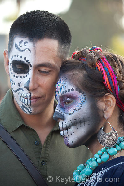A couple with half-calavera face paint at the Dia de Los Muertos celebration at Hollywood Forever Cemetery in Hollywood, CA