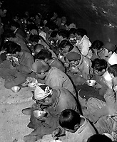 Communist guerrillas and their families, captured and brought down from Mt. Chirisan, by elements of the ROK Captiol Division, are fed in the POW stockade, Kurije, Korea.  December 12, 1951.  Cpl. Paul E. Stout. (Army)<br /> NARA FILE #:  111-SC-386498<br /> WAR & CONFLICT BOOK #:  1495