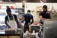 Pim Graham, 27,  (left) cooks food in the kitchen of Home Port, a restaurant in Chilmark/Menemsha, Martha's Vineyard, Massachusetts, USA, on Tues., July 25, 2017.   Home Port did not receive any H2B temporary foreign worker visas this year and has had difficulty filling all positions in the kitchen. On the day of this picture, one scheduled worker did not come to work and the restaurant could not find a backup to fill in. The restaurant has also quit serving lunch as a result of difficulty in finding workers. Graham is a Culinary Arts student from Jamaica who is working at the restaurant with a J1 foreign student worker visa. Graham says he worked at the restaurant for seven seasons. Peddie has an H2B visa. This is Peddie's first season working in the US.
