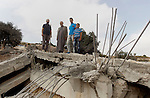 Palestinians inspect the rubble of the home of Mohammed Abed Almajid El-Amaira, a Palestinian accused of involvement in a shooting attack that led to the death of a rabbi, after it was destroyed by Israeli military on August 30, 2016 in the West Bank village of Dura near Hebron. Israel frequently destroys the homes of Palestinians who have carried out attacks. Amaira, a member of the Palestinian Authority security services, was arrested several weeks ago, accused of having helped plan and carry out the attack on July 1, when gunmen opened fire on a car near Hebron. The car crashed, killing rabbi Michael Mark, who led a religious school in the Israeli settlement of Otniel, and wounding two family members, according to the army. Photo by Wisam Hashlamoun
