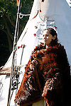 A Native American Lakota Sioux Indian woman in a buffalo robe by a tipi