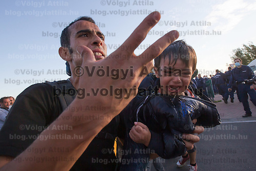 Illegal migrant father carries his crying child after they were sprayed with tear gas when a group of migrants tried to break out and run away from custody through a line of police officers near Roszke (about 174 km South of capital city Budapest), Hungary on September 07, 2015. ATTILA VOLGYI