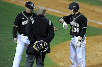 Designated hitter Mack Nathanson (34) of the Wofford College Terriers shows umpire T.R. Sloan where he was hit by a pitch in a game against the Boston College Eagles on Friday, February 13, 2015, at Russell C. King Field in Spartanburg, South Carolina. Wofford head coach Todd Interdonato is at left. Nathanson was awarded the base. Wofford won, 8-4. (Tom Priddy/Four Seam Images)