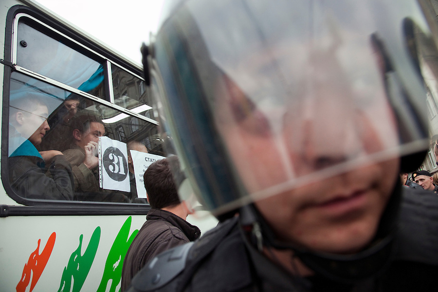 Moscow, Russia, 31/08/2010..Arrested demonstrators wave and hold posters in a police van as police break up an opposition protest in central Moscow and arrest around 70 people. Opposition activists hold regular demonstrations on the 31st day of the month, protesting against restrictions on the freedom of assembly, which is protected by article number 31 of the Russian constitution.