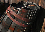 A old wine barrel leaned up against a old barn in Napa Valley California