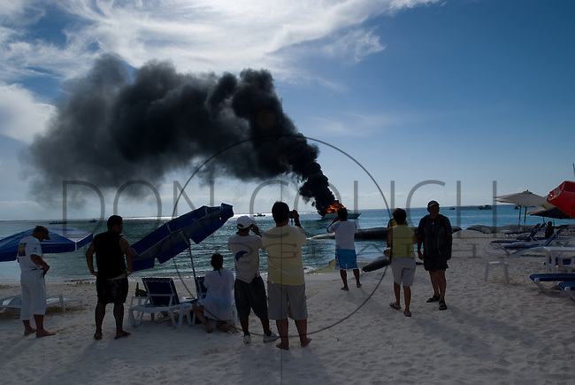 A crowd watches a boat on fire in the waters off Playa Norte, Isla Mujeres, Mexico.
